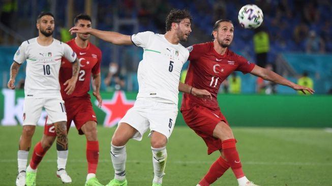 Gelandang Timnas Italia, Manuel Locatelli (tengah) berebut bola dengan gelandang Turki, Yusuf Yazici (kanan) pada laga Grup A Euro 2020 di Stadio Olimpico, Roma, Sabtu (12/6/2021) dini hari WIB. [ALBERTO LINGRIA / POOL / AFP]